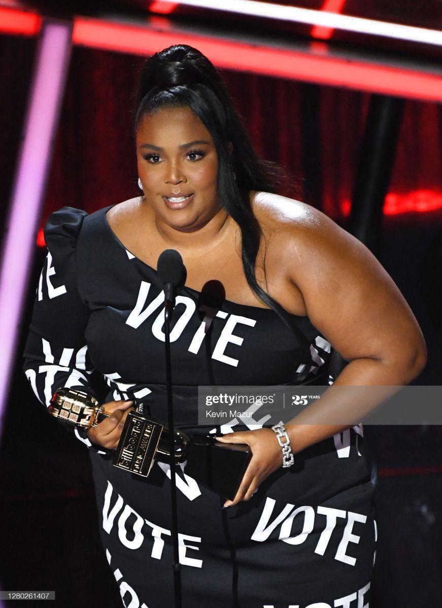 A cantora Lizzo recebendo prêmio do Billboard Awards usando um vestido com a palavra