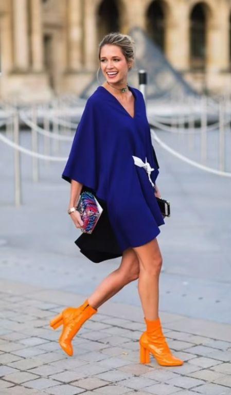 A modelo usa botas em tom laranja, o que contrasta com o classic blue usado no vestido.