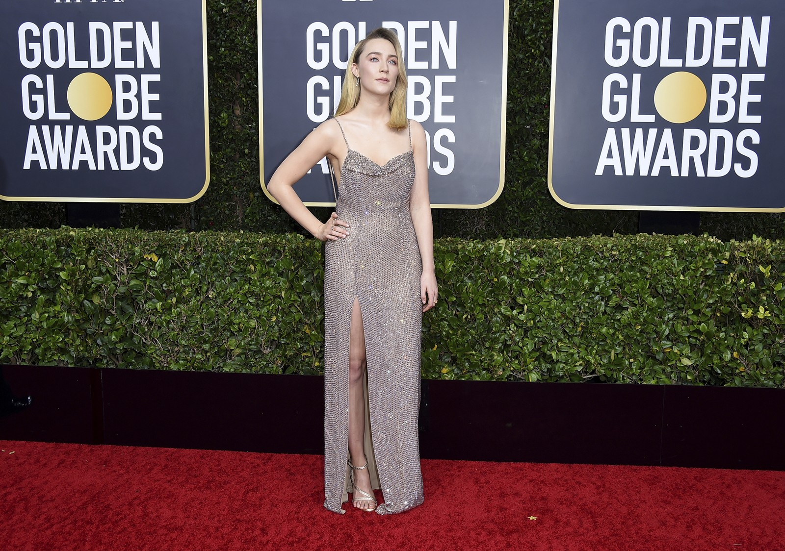 Saoirse Ronan posou no tapete vermelho do Golden Globes, com o vestido de alcinhas finas, sem volume e uma fenda lateral. — Foto: Jordan Strauss/AP