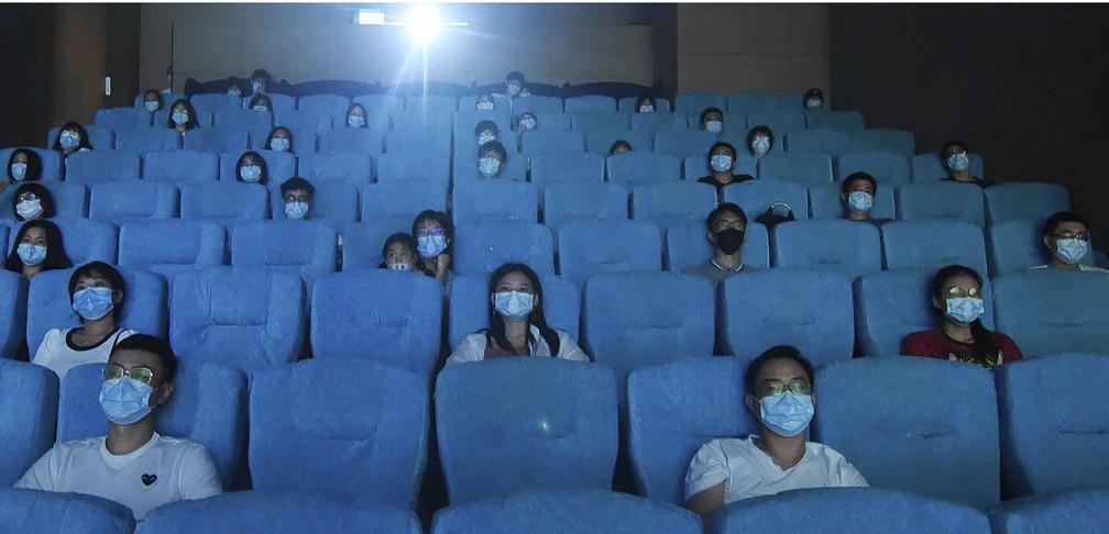 Público usa máscara enquanto assiste a filme em um cinema recém-reaberto na China. (Foto: Reprodução/ Chinatopix via AP/ G1)