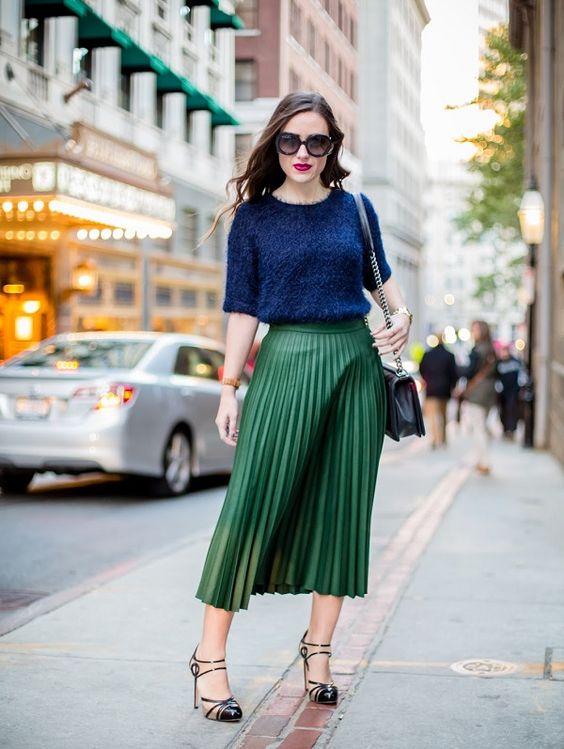 Saia plissada verde, com sapatos de salto fino, e blusa em tom classic blue.